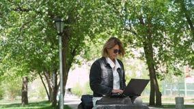 Mujer que se sienta en el banco en un parque y que usa el ordenador portátil almacen de video