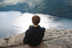 Mujer que se sienta en el borde de la colina Fotos de archivo libres de regalías