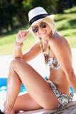 Mujer que se sienta en el borde de nadar en piscina Imagen de archivo libre de regalías