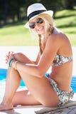 Mujer que se sienta en el borde de nadar en piscina Foto de archivo libre de regalías