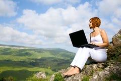 Mujer que se sienta en el borde de un acantilado con una computadora portátil Imagenes de archivo