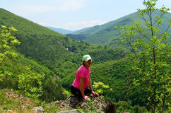 mujer que se sienta en el borde del acantilado que mira el Mountain View verde hermoso Fotografía de archivo