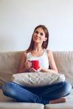 Mujer que se sienta en el café de consumición del sofá Foto de archivo libre de regalías