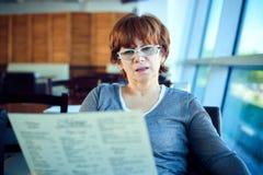 Mujer que se sienta en el café del aeropuerto y para la salida que espera Imagen de archivo libre de regalías