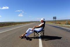 Mujer que se sienta en el camino Imagen de archivo
