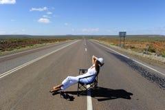 Mujer que se sienta en el camino Imagen de archivo libre de regalías