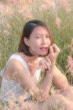 Mujer que se sienta en el campo de hierba imagen de archivo libre de regalías