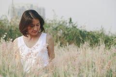 Mujer que se sienta en el campo de hierba imagenes de archivo