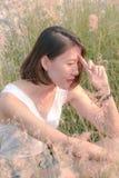 Mujer que se sienta en el campo de hierba imágenes de archivo libres de regalías
