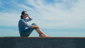 Mujer que se sienta en el cielo azul almacen de video