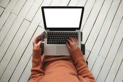 Mujer que se sienta en el cuarto con una tarjeta de crédito y un ordenador portátil, comprando en línea fotos de archivo libres de regalías