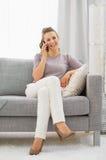 Mujer que se sienta en el diván y el teléfono celular que habla foto de archivo