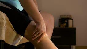 Mujer que se sienta en el dormitorio que frota su rodilla artrítica almacen de metraje de vídeo