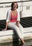 Mujer que se sienta en el embarcadero del puerto deportivo Foto de archivo libre de regalías