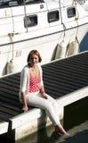 Mujer que se sienta en el embarcadero del puerto deportivo Imagenes de archivo