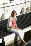 Mujer que se sienta en el embarcadero del puerto deportivo Fotografía de archivo