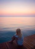 Mujer que se sienta en el embarcadero en la salida del sol imagenes de archivo