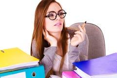 Mujer que se sienta en el escritorio en oficina y el pensamiento foto de archivo libre de regalías