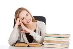Mujer que se sienta en el escritorio por completo de libros Imagenes de archivo