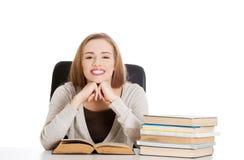 Mujer que se sienta en el escritorio por completo de libros Foto de archivo