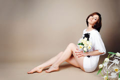 Mujer que se sienta en el estudio con los tulipanes de las flores blancas Fotos de archivo libres de regalías