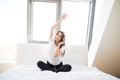 Mujer que se sienta en el extremo de la cama a Imagen de archivo libre de regalías