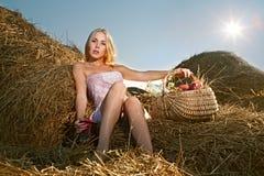 Mujer que se sienta en el heno Foto de archivo libre de regalías