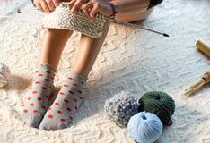 Mujer que se sienta en el hilo de algodón del piso que hace punto Imagen de archivo