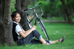 Mujer que se sienta en el jardín verde con el CCB de la bicicleta Imagen de archivo