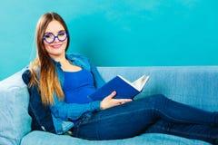 Mujer que se sienta en el libro de lectura del sofá en casa Imágenes de archivo libres de regalías