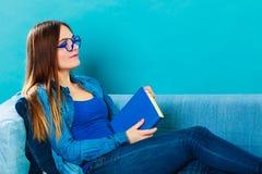 Mujer que se sienta en el libro de lectura del sofá en casa Imagenes de archivo