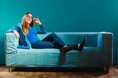 Mujer que se sienta en el libro de lectura del sofá en casa Fotos de archivo libres de regalías