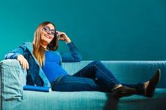 Mujer que se sienta en el libro de lectura del sofá en casa Foto de archivo
