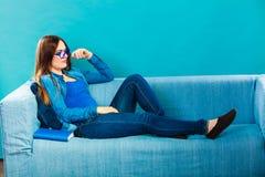 Mujer que se sienta en el libro de lectura del sofá en casa Fotografía de archivo libre de regalías