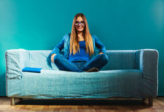 Mujer que se sienta en el libro de lectura del sofá en casa Imagen de archivo