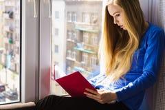 Mujer que se sienta en el libro de lectura del travesaño de la ventana en casa Imagenes de archivo