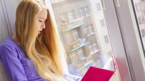 Mujer que se sienta en el libro de lectura del travesaño de la ventana en casa Fotografía de archivo