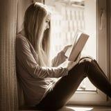Mujer que se sienta en el libro de lectura del travesaño de la ventana en casa Foto de archivo