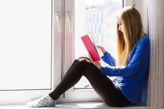 Mujer que se sienta en el libro de lectura del travesaño de la ventana en casa Fotografía de archivo libre de regalías