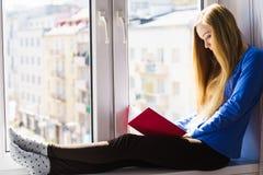 Mujer que se sienta en el libro de lectura del travesaño de la ventana en casa Fotos de archivo libres de regalías