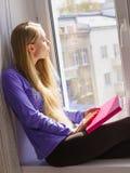 Mujer que se sienta en el libro de lectura del travesaño de la ventana en casa Imágenes de archivo libres de regalías