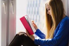 Mujer que se sienta en el libro de lectura del travesaño de la ventana en casa Foto de archivo libre de regalías