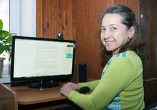 Mujer que se sienta en el ordenador Foto de archivo