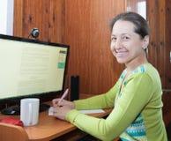 Mujer que se sienta en el ordenador Fotografía de archivo