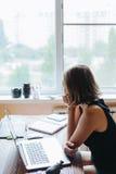 Mujer que se sienta en el ordenador y que mira hacia fuera la ventana Foto de archivo libre de regalías