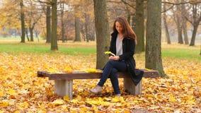 Mujer que se sienta en el parque del otoño, juego con la hoja de arce caida almacen de metraje de vídeo