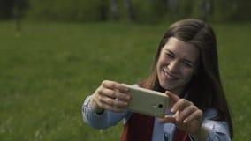 Mujer que se sienta en el parque y que hace Selfie almacen de metraje de vídeo