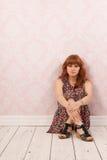 Mujer que se sienta en el piso Foto de archivo libre de regalías