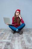 Mujer que se sienta en el piso con el ordenador portátil Imagen de archivo libre de regalías
