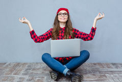 Mujer que se sienta en el piso con el ordenador portátil y meditar Imagen de archivo libre de regalías